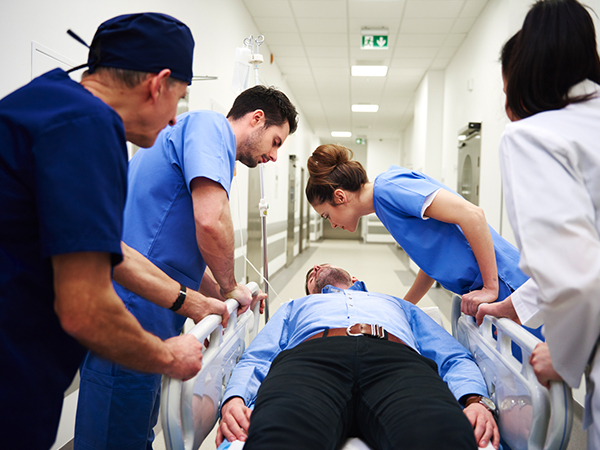Hospital image of male on gurney with doctors overlooking while rolling him down the hall